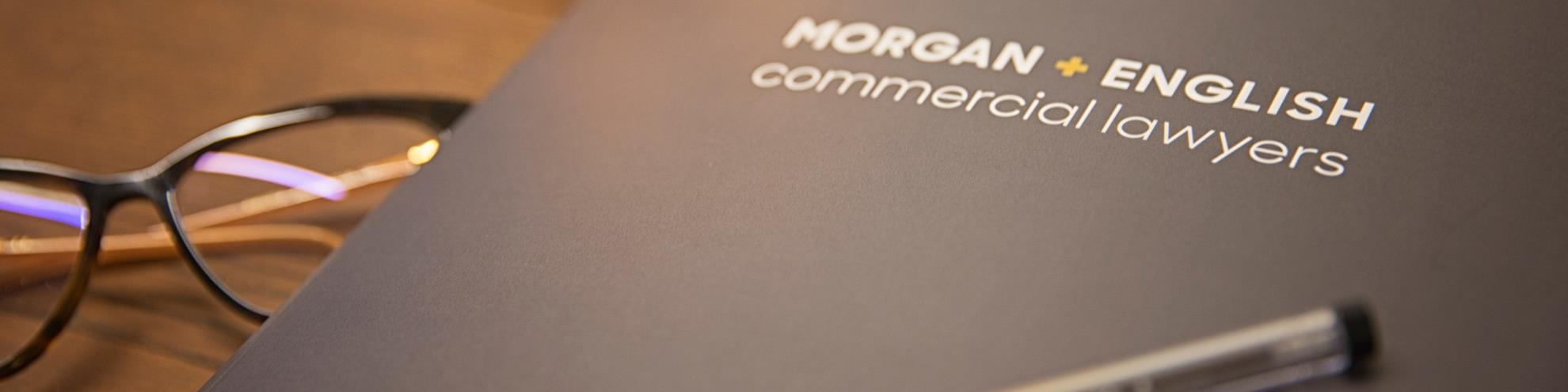Morgan English Commercial Lawyers folder, pen and glasses